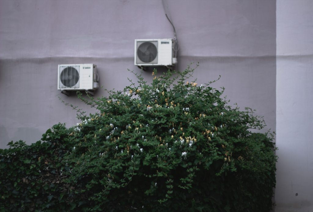 photo of air conditioning units attached to an exterior wall with a green bush underneath