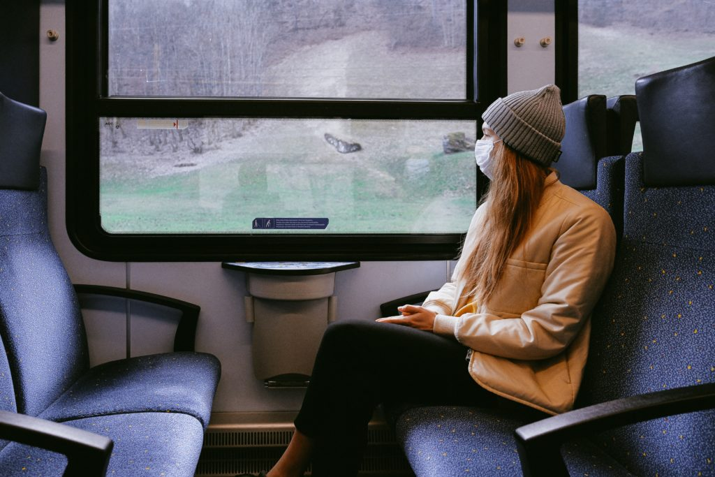 a woman wearing a mask, sitting on a train and looking out the window