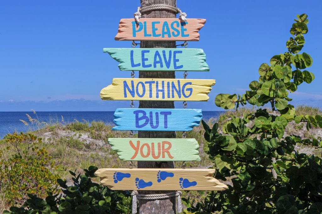 a sign on the beach that depicts a sustainable tourism message, to please leave nothing but your footprints